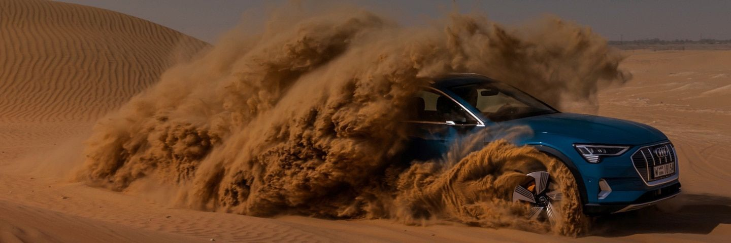Audi e-tron spinning up sand during a desert drive