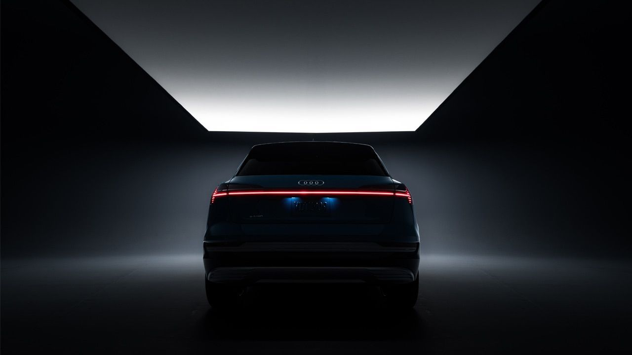 The Audi e-tron in a dimly lit studio showing its horizontal tailight that stretches across the entire rear of the vehicle.
