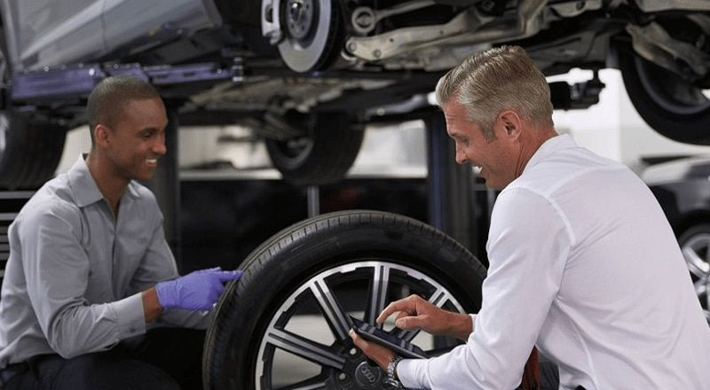 Two Audi engineers providing maintenance on an Audi tire.