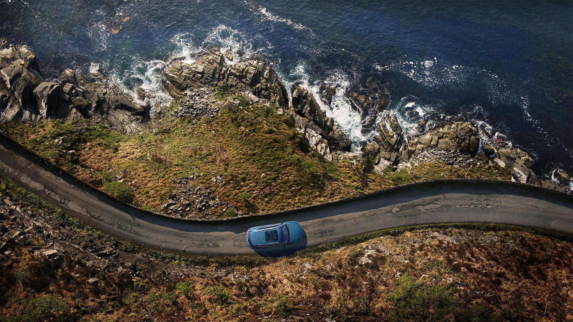 Image of an e-tron SUV driving along a costal road on the side of the ocean.