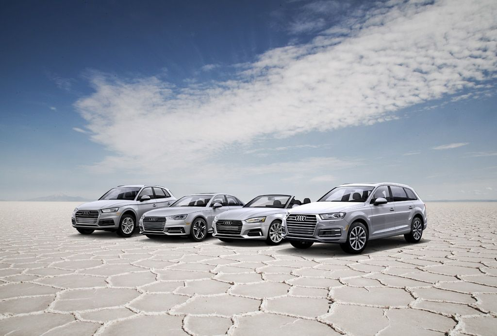 The four Silvercar fleet vehicles parked on a plain in front of a blue sky.